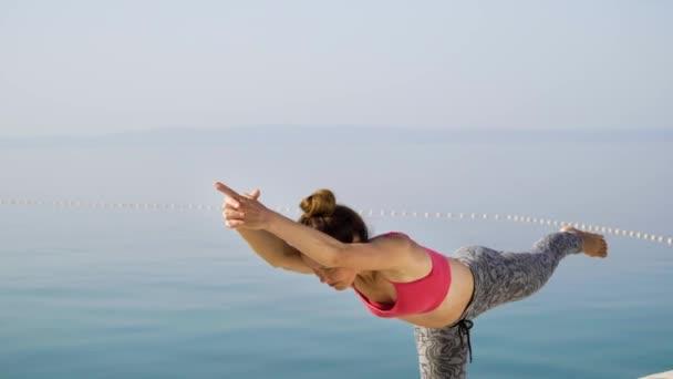 fröhliche athletische Frau praktiziert Yoga auf der Seebrücke