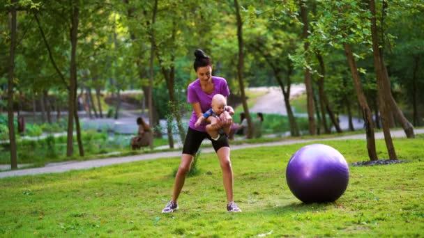 Sportliche Frau trainiert im Park mit Baby an den Händen