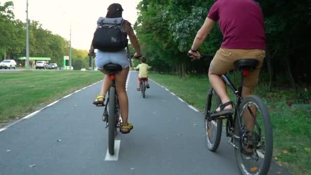 Rodiče a děti na kolech společně v letní den