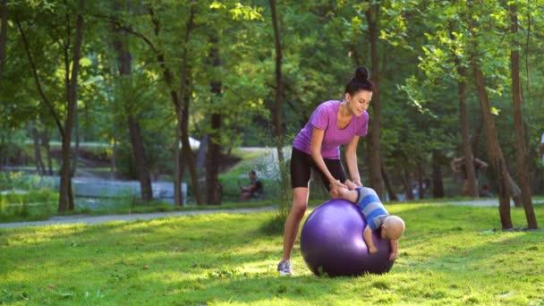 Mutter und Baby turnen auf Fitnessball im Park