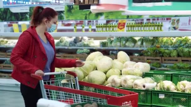 Woman in medical mask picking cabbage at grocery store