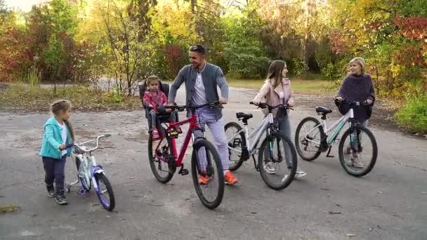 Fit rodina procházky s koly v parku na začátku podzimu