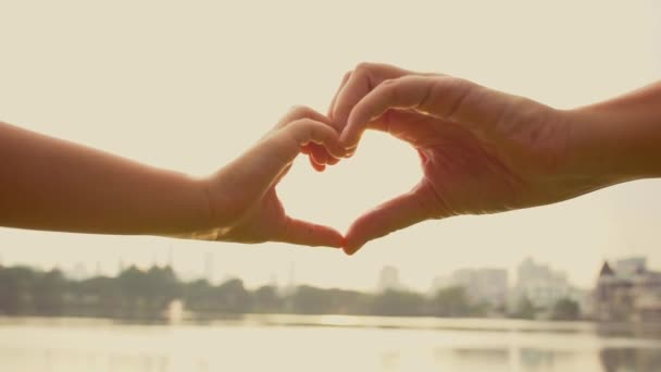 Mother and child making heart shape with hands at sunset. Love symbol gesture with orange sun flare