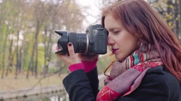 Fiatal, vonzó nő, aki digitális kamerával fényképez az őszi parkban