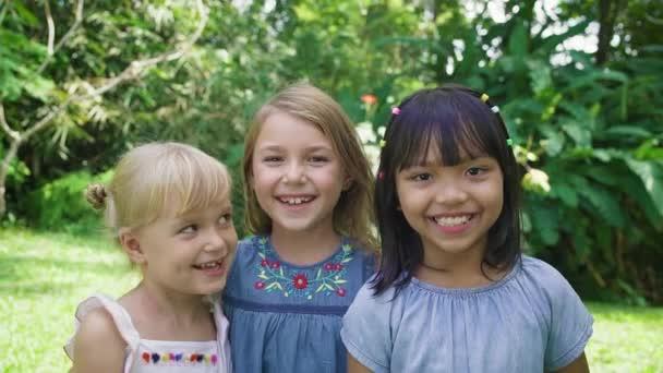 Nahaufnahme von drei süßen lächelnden muliethnischen Mädchen, die im Park in die Kamera schauen.