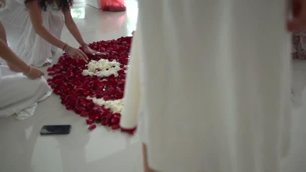Womens kezek hozzon létre egy Mandala a rózsaszirom formájában a Yin yang szimbólum a fehér padlón