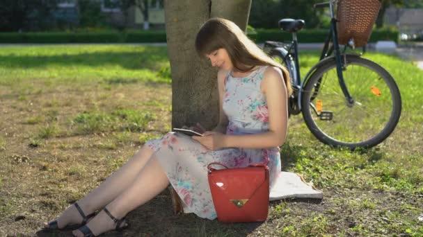 fiatal nő használ tabletta, olvasás e-könyv a parkban, nyári vakáció, diák