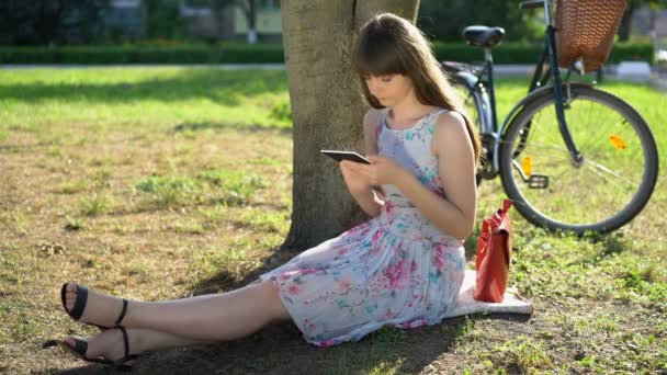 Beautiful woman sitting on grass in park, using tablet, surfing web, reading