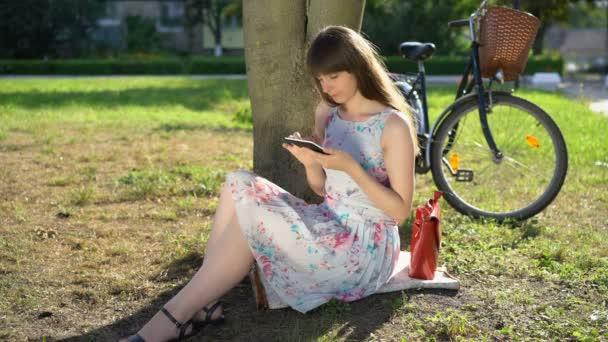 Studentin liest im Sommer E-Book im Stadtpark, studiert, College-Leben
