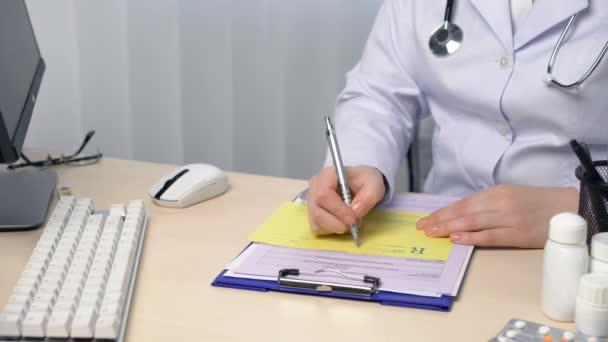 Arzt füllt Rezeptformular in seinem Büro aus, verschreibt Medikamente