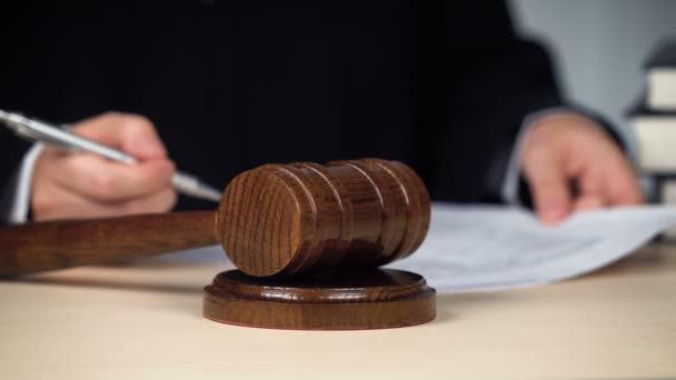 Giudico firma carte, annunciando il giudizio, colpendo gavel per chiudere il procedimento