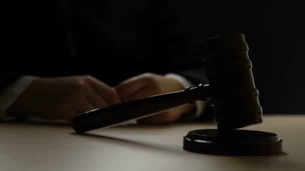 Hands of corrupt judge striking gavel in dark courtroom, corruption, bribes