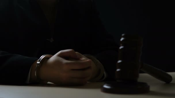 Handcuffed hands of corrupt judge sitting in dark courtroom, injustice, bribery