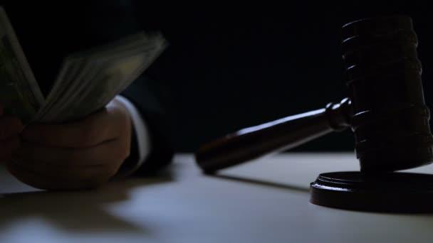 Corrupt judge or auctioneer counting money in dark room, black market, criminal