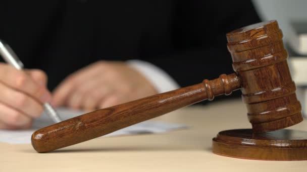 Giudice o banditore che compila moduli, firma documenti alla scrivania in aula