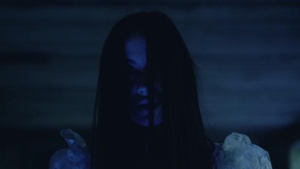 Ďábelský úsměv na tváři čarodějnice v temnotě, rituál černé magie, nadpřirozená moc
