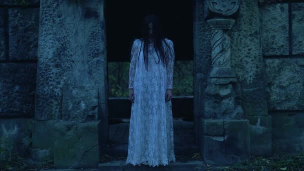 Creepy ghost in white dress near ancient stone crypt, rising from dead