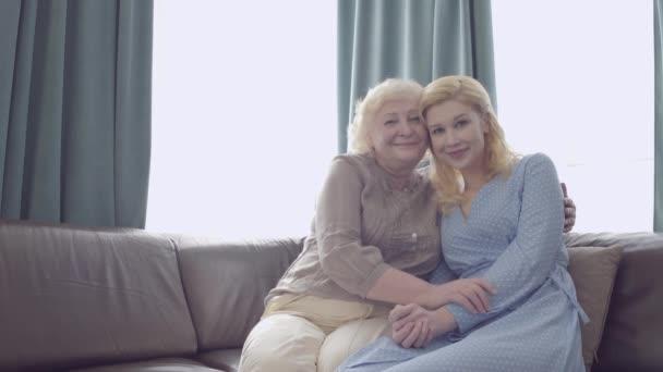 Milující starší matka a dcera objímání, při pohledu na kameru, rodinné spojení