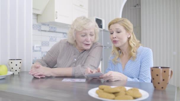 Ältere Frau und Tochter sehen sich zu Hause Fotos an und verbringen Zeit miteinander
