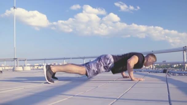 Mužský atlet dělá kliky na střeše, pevnost horní části těla, venkovní cvičení