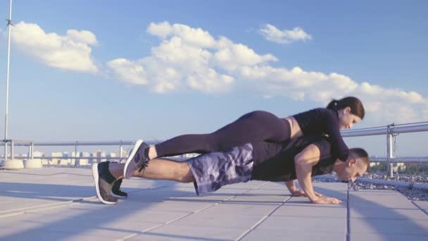 Mladý sportovec dělá kliky s přítelkyní na ramenou, cvičení s váhou