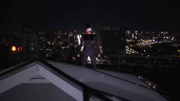 Gefährliche maskierte Verbrecherin, die nachts auf Dach steht, bereit für den Angriff