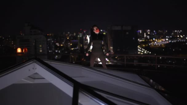 Statečná dívka v přestrojení stojící na střeše domu, připravená bojovat proti zločinu