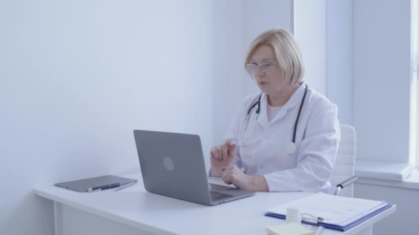 Female doctor talking to patient online by laptop app, remote consultation