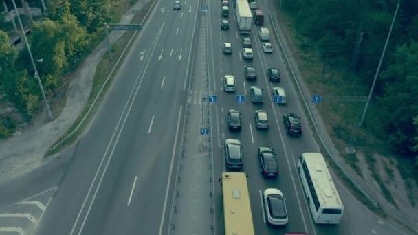 Mnoho automobilů a veřejné dopravy se pohybuje pomalu v dopravní zácpě, dojíždění do města
