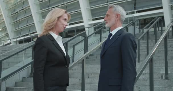Male and female business partners shaking hands outdoors, start of cooperation