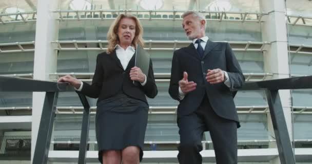 Muž magnát a žena asistent kráčet dolů kontrolu realitní projekt