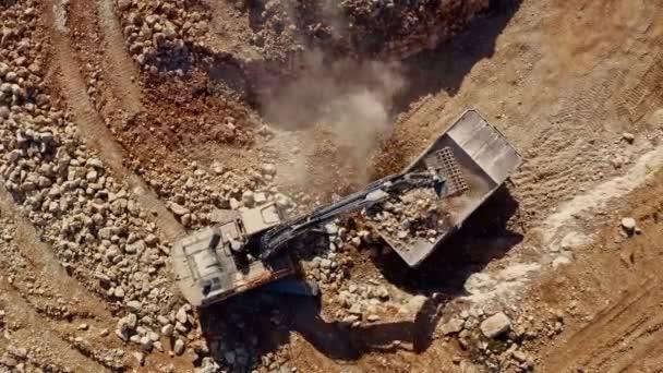 Zeitraffer der Verladung von Steinen durch Bagger auf LKW auf einer zukünftigen Baustelle, Drohnenaufnahme aus der Luft 4k