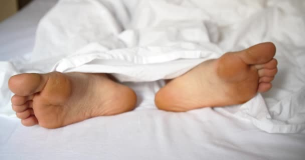 man sleeping in bed, feet close up.