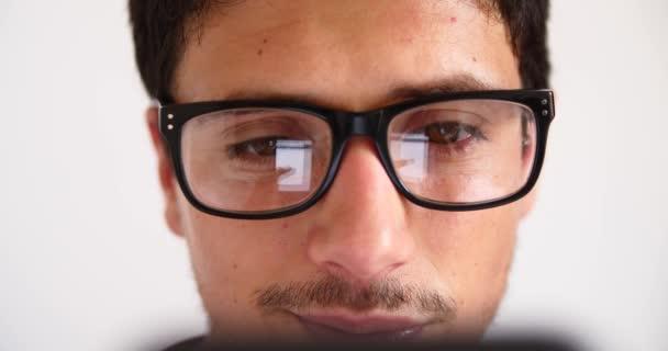 Atraktivní mladý muž pomocí smartphone, zatímco konverzace, psaní, reflexe očí v brýlích zblízka.