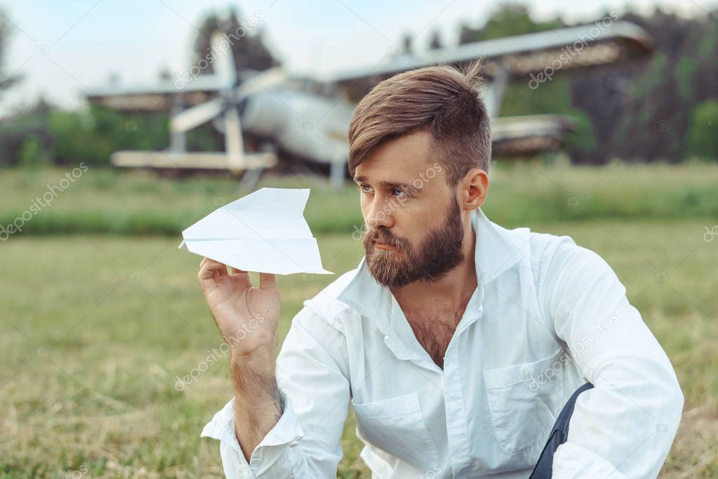 man launches paper airplanes sitting on the grass