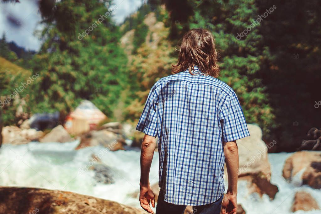 the guy stands at the mountain river