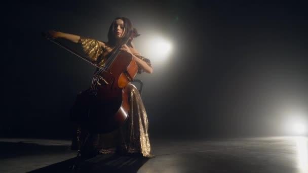 Violoncellistou provádí na jevišti.