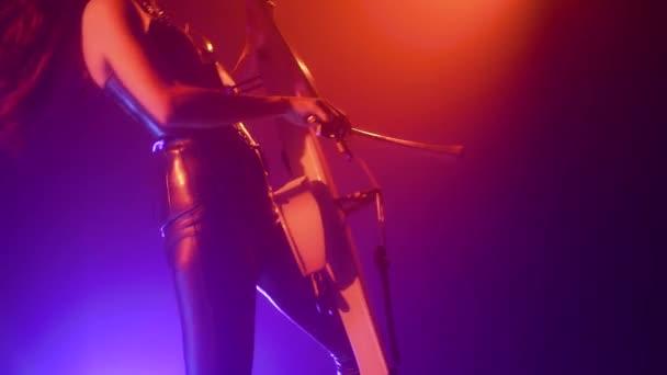 Violoncellista s elektronickým violoncello provádí na jevišti.