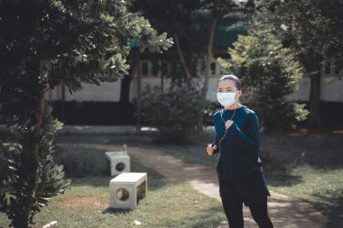 Portrait of Asian woman running at village park listening to music and wearing mask. Woman wearing mask for protective pollution and protection virus, coronavirus and running at park.