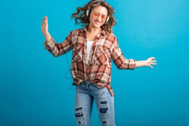 attractive woman smiling enjoying listening to music in headphones in checkered shirt and jeans isolated on blue studio background, wearing pink sunglasses