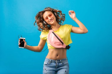 attractive smiling happy woman dancing listening to music in headphones dressed in hipster stylish outfit isolated on blue studio background, wearing colorful clothes in summer style, having fun