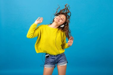 attractive smiling happy woman dancing listening to music in headphones in hipster stylish outfit isolated on blue studio background, wearing shorts and yellow sweater in summer style, having fun