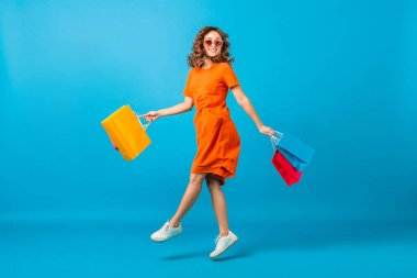 attractive stylish woman jumping with shopping bags colorful on blue background