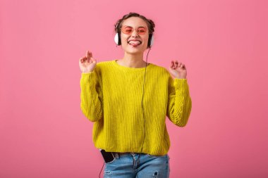 happy funny woman listening to music in headphones dressed in hipster colorful style outfit isolated on pink studio background, wearing yellow sweater and sunglasses, having fun showing tongue