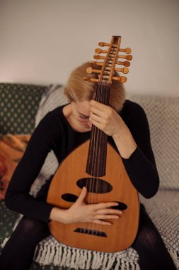 young beautiful woman artist at home with lute
