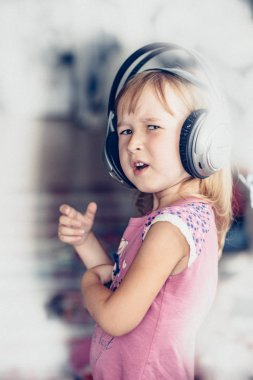 cute little girl singing while listening music in headphones