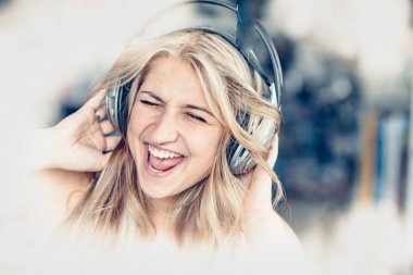 emotional young woman listening music in headphones