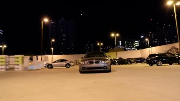 Pohyblivé kamery záběr Bmw auto k fotoaparátu v parkovišti v noci