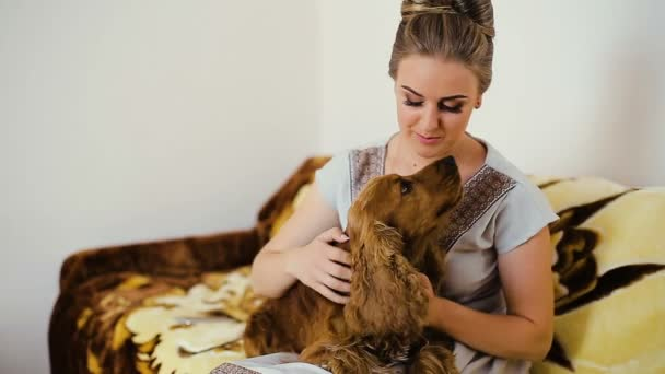 Woman and dog cocker spaniel. He strokes, touches, hugs, kisses, smiles