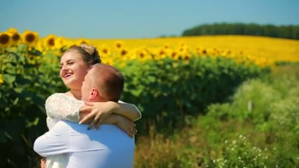 Happy couple running on sunflower field, taking hands and smiling.